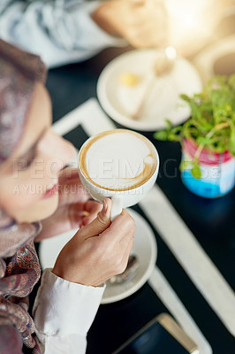 Buy stock photo High angle shot of a young woman having a creamy cup of coffee in a cafe