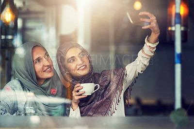 Buy stock photo Shot of two women taking selfies with a mobile phone in a cafe
