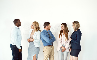 Buy stock photo Studio shot of a group of confident work colleagues standing and looking a each other against a white background
