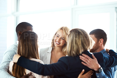 Buy stock photo Shot of a group of work colleagues forming a huddle together while standing in the office during the day