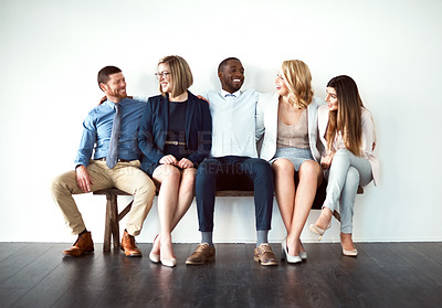 Buy stock photo Shot of a group of work colleagues seated next to each other against a white background