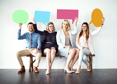 Buy stock photo Shot of a group of work colleagues seated next to each other while holding speech bubbles against a white background