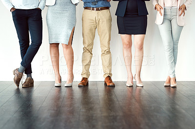 Buy stock photo Low angle shot of a group of unrecognizable work colleagues standing with their arms folded against a white background