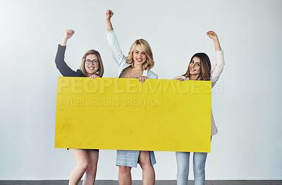 Buy stock photo Studio shot of a group of businesswomen holding up a blank yellow placard and cheering