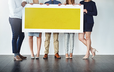 Buy stock photo Cropped studio shot of a group of businesspeople holding up a blank yellow placard