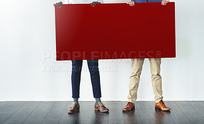 Buy stock photo Cropped studio shot of two businessmen holding up a blank red placard