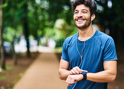 Buy stock photo Shot of a sporty young man checking his watch while exercising outdoors
