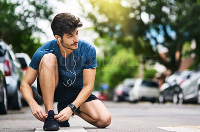 Buy stock photo Shot of a sporty young man tying his shoelaces while exercising outdoors