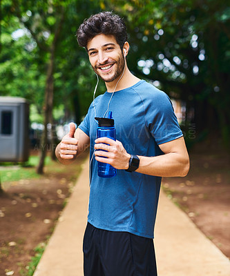 Buy stock photo Portrait of a sporty young man holding a water bottle and showing thumbs up while exercising outdoors