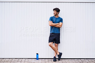 Buy stock photo Shot of a sporty young man standing against a white wall
