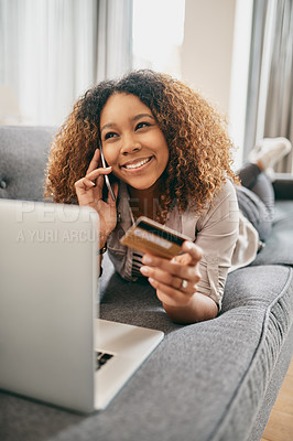 Buy stock photo Shot of a cheerful young woman doing online shopping on her laptop while talking on her cellphone at home