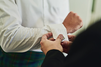 Buy stock photo Shot of an unrecognizable man's hands folding another man's sleeve to get ready for a wedding