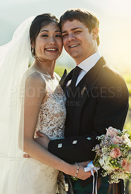 Buy stock photo Portrait of a cheerful young bride and groom holding each other while standing outside on a farm