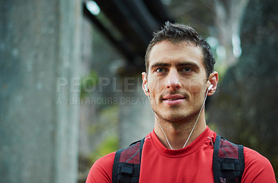 Buy stock photo Cropped shot of a handsome young man listening to music while out for  run