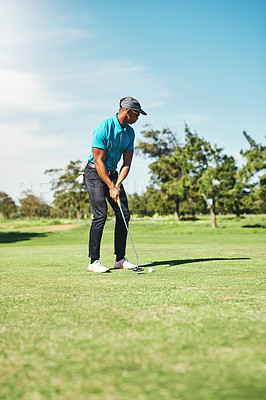 Buy stock photo Shot of a focused young male golfer about to play a shot with his putter on a golf course outside during the day
