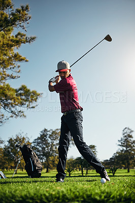 Buy stock photo Shot of a focused young male golfer about to swing and play a shot with his golf club outside on a course