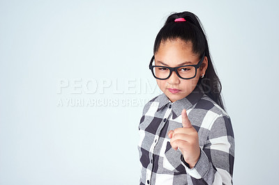 Buy stock photo Studio portrait of a cute young girl pointing her finger with attitude against a gray background
