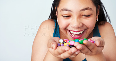 Buy stock photo Studio shot of a cute young girl holding a handful of colorful jelly beans