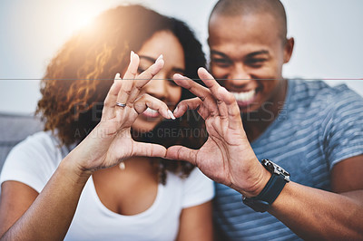 Buy stock photo Shot of a young couple making a heart shape with their fingers at home