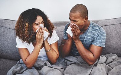 Buy stock photo Shot of a young couple blowing their noses at home