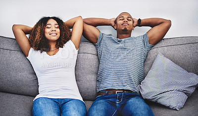 Buy stock photo Shot of a young couple resting on a couch at home