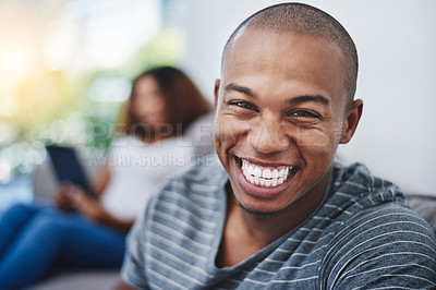 Buy stock photo Portrait of a young man relaxing at home with his girlfriend in the background