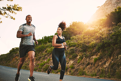 Buy stock photo Shot of a young couple out running together