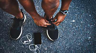 Buy stock photo Cropped shot of an unrecognizable man tying his shoelaces