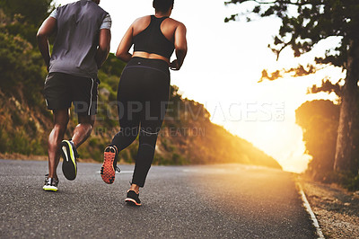 Buy stock photo Rearview shot of a young couple out running together