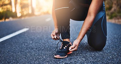 Buy stock photo Cropped shot of an unrecognizable woman tying her shoelaces
