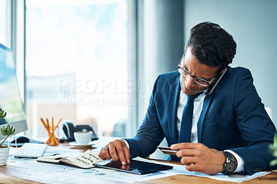 Buy stock photo Shot of a focused young businessman seated at his desk while talking on the phone and browsing on a digital tablet in the office