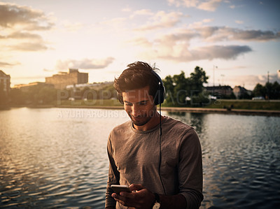 Buy stock photo Cropped shot of a young man listening to music on his cellphone outside