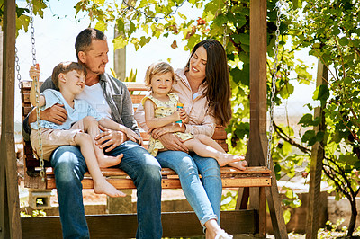 Buy stock photo Shot of a family of four relaxing together on a garden swing