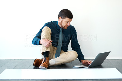 Buy stock photo Full length shot of a handsome mature male architect working on his laptop
