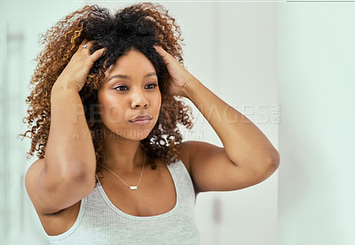 Buy stock photo Shot of a confident young woman holding her hair while looking at herself in the mirror inside of a bathroom at home