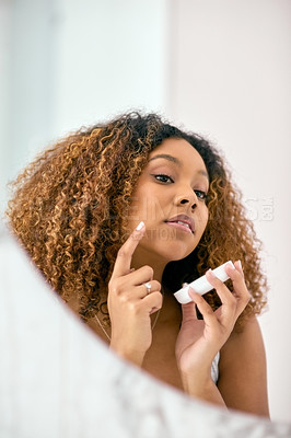Buy stock photo Shot of a confident young woman applying skin cream on her face while looking into the mirror in the bathroom at home