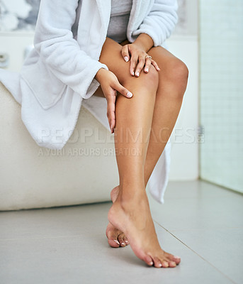 Buy stock photo Shot of an unrecognizable woman holding her freshly shaved leg while being seated in the bathroom at home