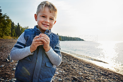 Buy stock photo Cropped shot of an adorable young boy playing outside near a lake