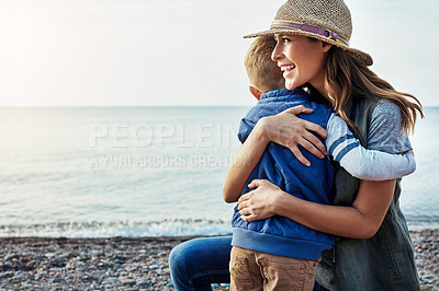 Buy stock photo Shot of a loving mother hugging her son while out by the lake