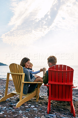 Buy stock photo Shot of a young family enjoying a day at the lake