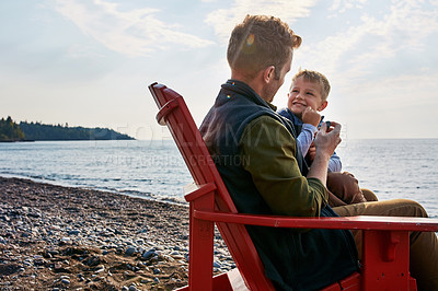 Buy stock photo Shot of a handsome young father and his son enjoying a day by the lake
