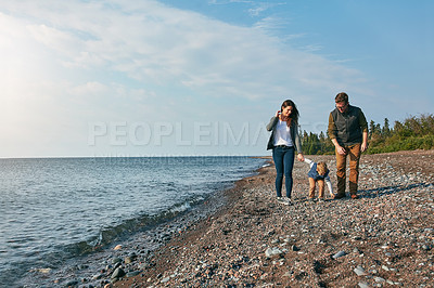 Buy stock photo Shot of a young family walking by the lake
