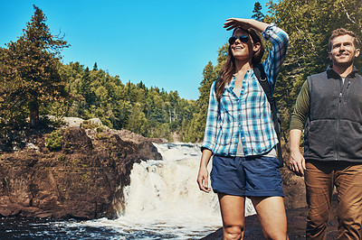 Buy stock photo Shot of a young couple walking next to a rocky river and waterfall