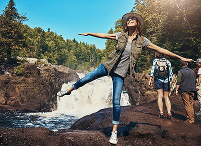 Buy stock photo Shot of a young woman having fun next to a rocky river and waterfall with her friends in the background