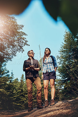 Buy stock photo Shot of a young couple going for a hike through nature