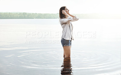 Buy stock photo Shot of an attractive young woman standing in a lake
