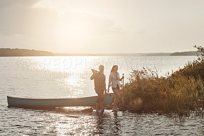 Buy stock photo Shot of a young couple going for a canoe ride on the lake