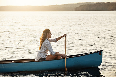Buy stock photo Shot of a beautiful young woman rowing a boat out on the lake