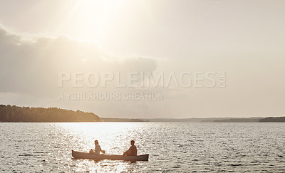 Buy stock photo Shot of an unrecognizable couple rowing a boat out on the lake