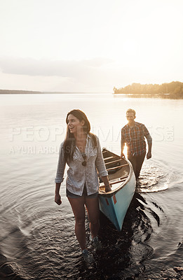 Buy stock photo Shot of a young couple coming from a canoe ride on the lake